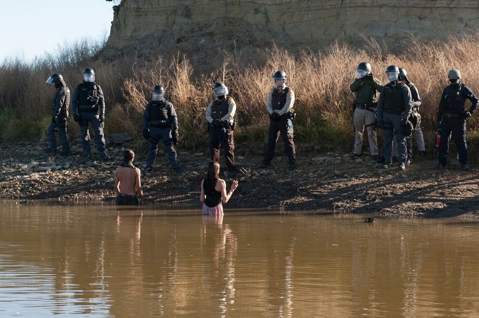 Two people stand in the water of a river while police officers guard the shore.