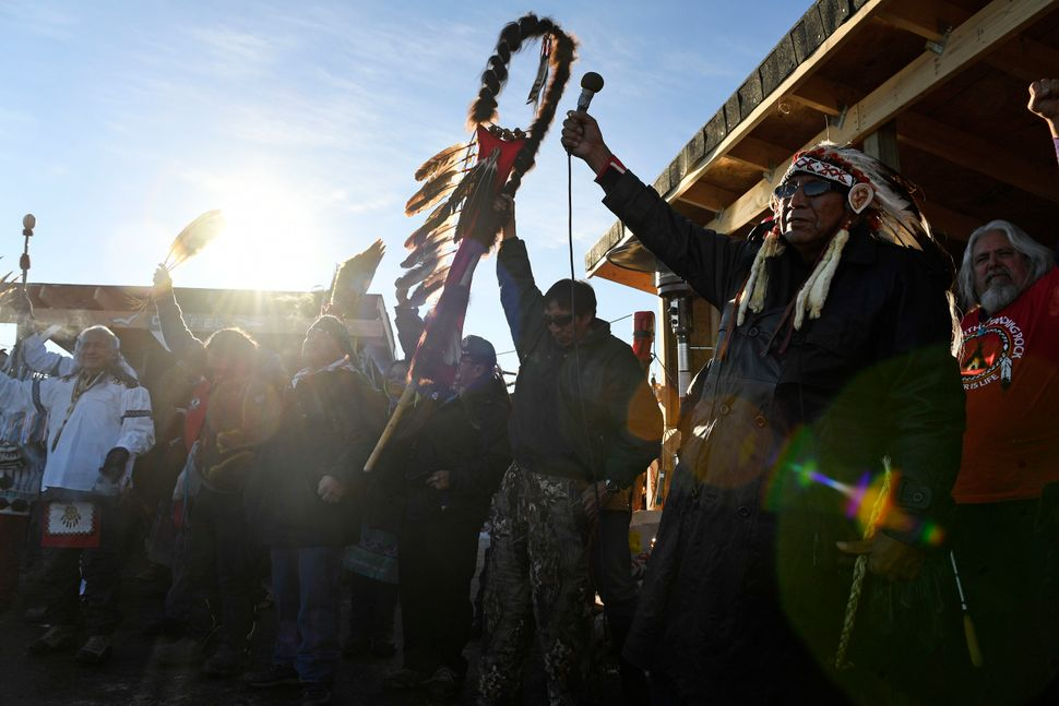 Native Americans lift up their hands to celebrate their victory after the US Army Corps of Engineers shut down the