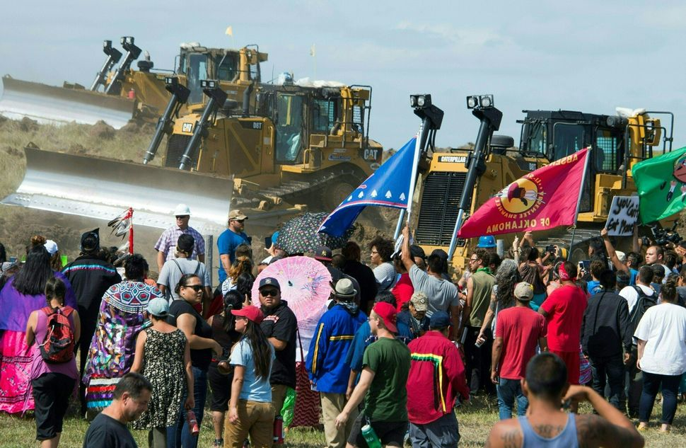 Members of the Standing Rock Sioux Tribe and their supporters confront bulldozers working on the oil pipeline.