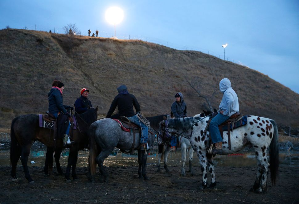 Riders bring their horses to the edge of the water for a drink as police stand atop the hill on Turtle Island.