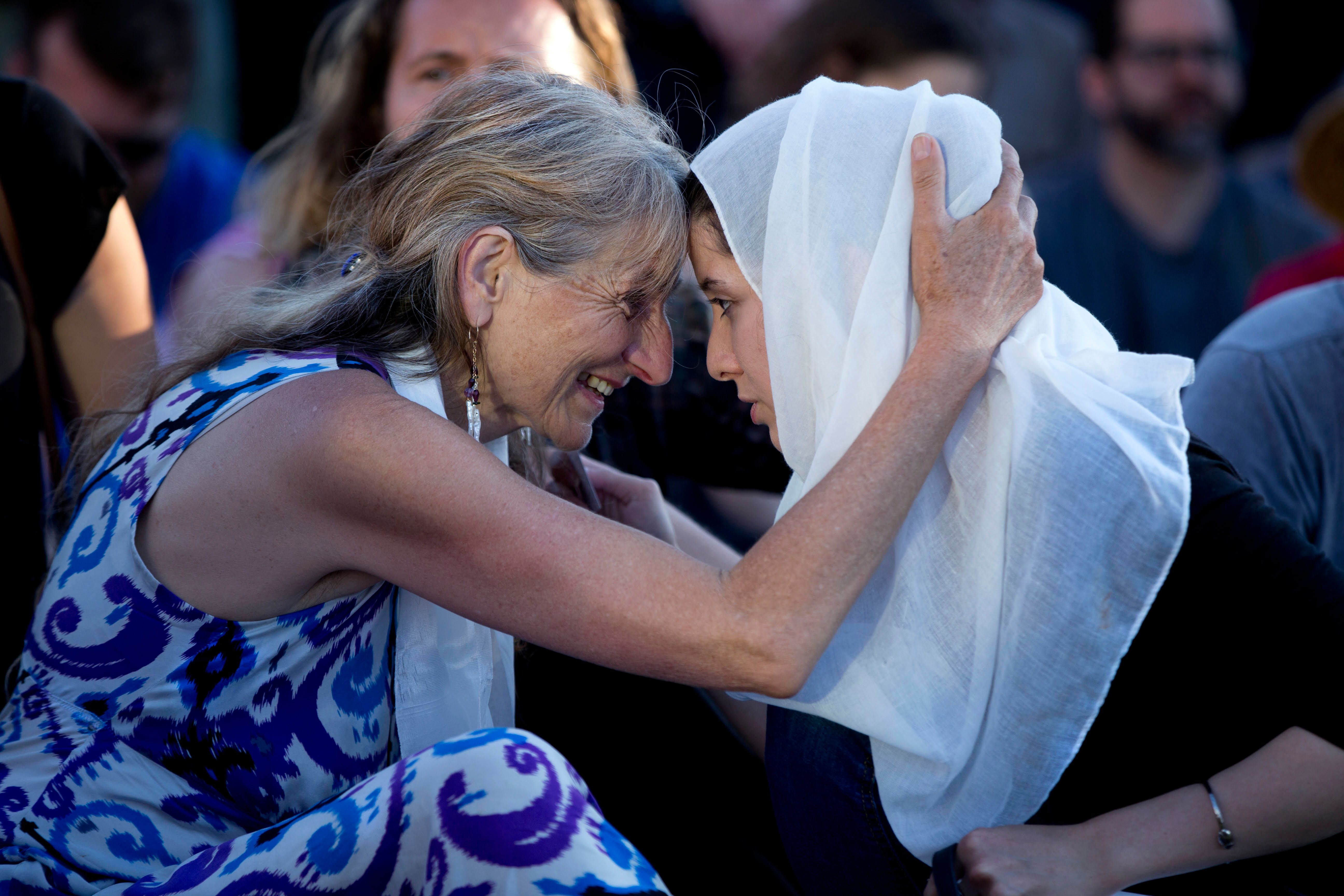 Asha Deliverance, left, the mother of Taliesin Myrddin Namkai-Meche, leans in and embraces a woman who...