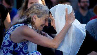Asha Deliverance, left, the mother of Taliesin Myrddin Namkai-Meche, leans in and embraces a woman who approached her at the vigil. A vigil was held Saturday in Portland at the MAX station where two men, Rick John Best, 53, of Happy Valley and Taliesin Myrddin Namkai-Meche, 23, of Southeast Portland, were murdered and a third man, Micah David-Cole Fletcher, 21, was wounded in an attack Friday.  May 27, 2017 Beth Nakamura/Staff