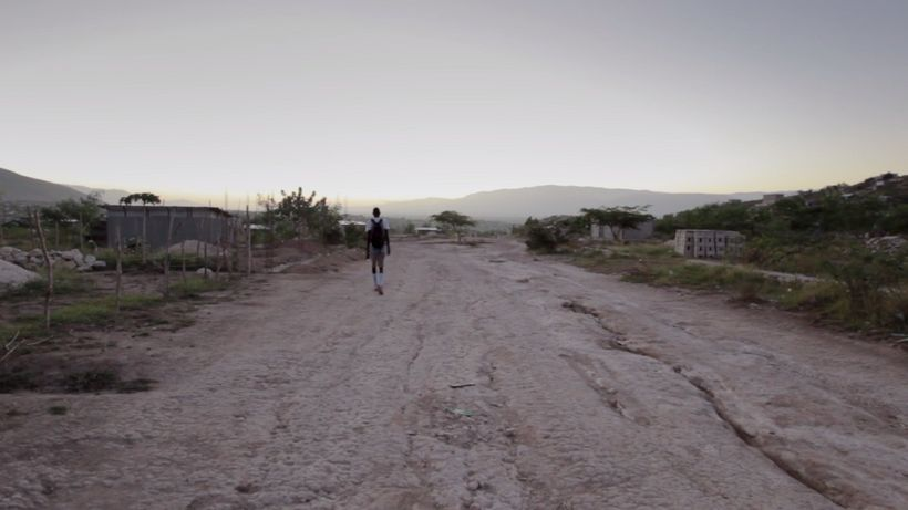 Pierre Joseph walking on the outskirts of Port-Au-Prince, Haiti to the basketball court