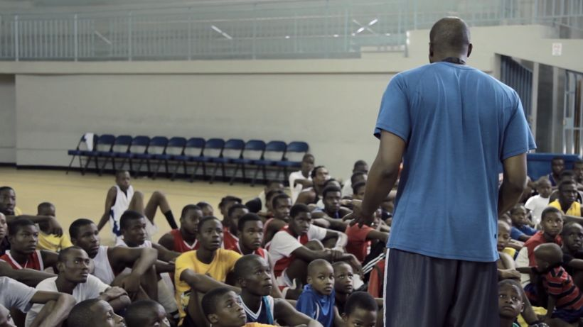 Pierre Valmera giving a speech to a group of aspiring basketball players in Haiti
