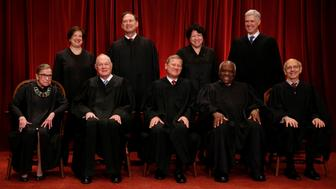 U.S. Chief Justice John Roberts (seated C) leads Justice Ruth Bader Ginsburg (front row, L-R), Justice Anthony Kennedy, Justice Clarence Thomas, Justice Stephen Breyer, Justice Elena Kagan (back row, L-R), Justice Samuel Alito, Justice Sonia Sotomayor, and Associate Justice Neil Gorsuch in taking a new family photo including Gorsuch, their most recent addition, at the Supreme Court building in Washington, D.C., U.S., June 1, 2017. REUTERS/Jonathan Ernst