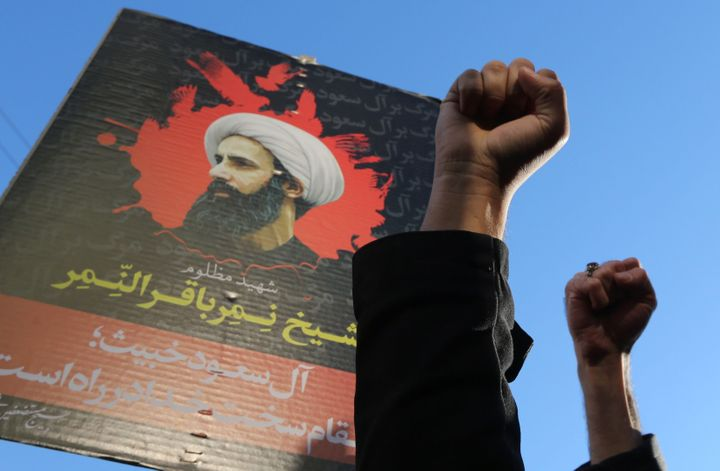 Iranian protesters raise their fists in front of a portrait of prominent Shiite Muslim cleric Nimr al-Nimr during a demonstra