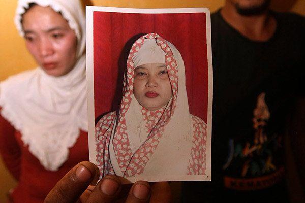 Irwan Setiawan along with his sister Evi Kurniati holds a picture of his mother Ruyati Binti Sapubi in their house in Bekasi