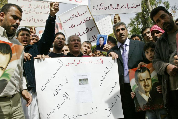 Syrians carry banners and a portrait of Syrian President Bashar al-Assad (R) during a demonstration in Tishrin Park in downto