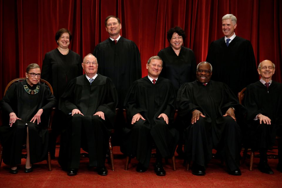 U.S. Supreme Court Justice Anthony Kennedy (bottom 2nd L) reacts while chatting with Chief Justice John Roberts (C) during a