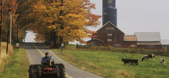 <em>Tractor on farm road with barn and silo in background in autumn, VT</em>
