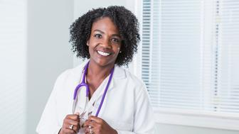 Portrait of an African-American female doctor. She is standing, smiling confidently at the camera, wearing a white lab coat with a stethoscope around her neck.  She is a mature woman in her 40s.