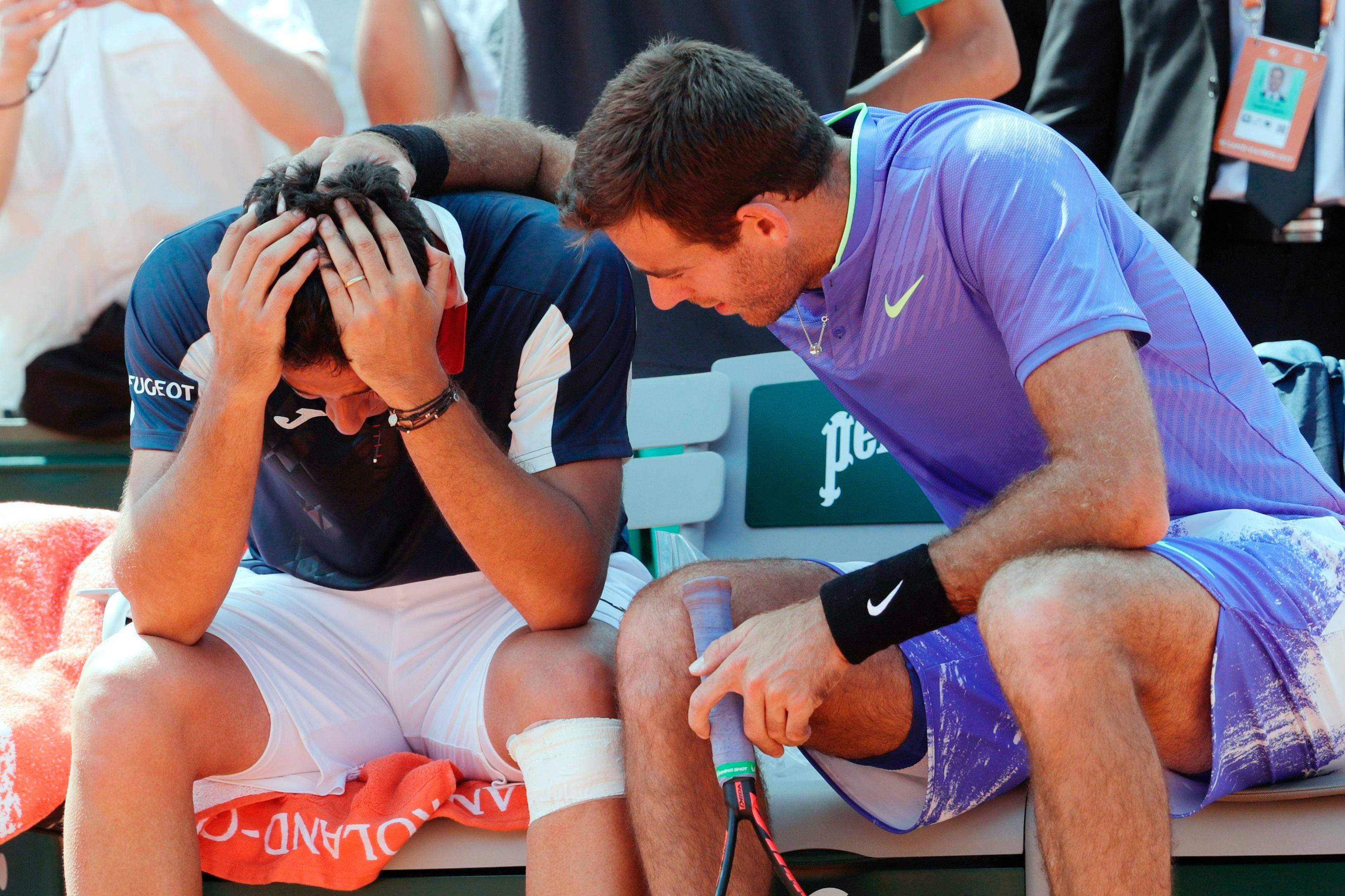 Spain's Nicolas Almagro (L) is comforted by Argentina's Juan Martin Del Potro as he has to give up due to an injury during their tennis match at the Roland Garros 2017 French Open on June 1, 2017 in Paris.  / AFP PHOTO / Thomas SAMSON        (Photo credit should read THOMAS SAMSON/AFP/Getty Images)