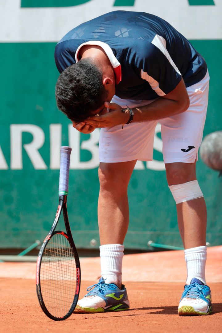 Almagro reacts as he realizes he can't finish the match. The player has been fighting a recurring knee injury.