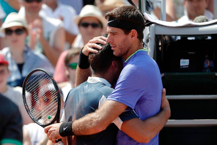 Spain's Nicolás Almagro, left, is comforted by Argentina's Juan Martín del Potro as a knee injury forces him to