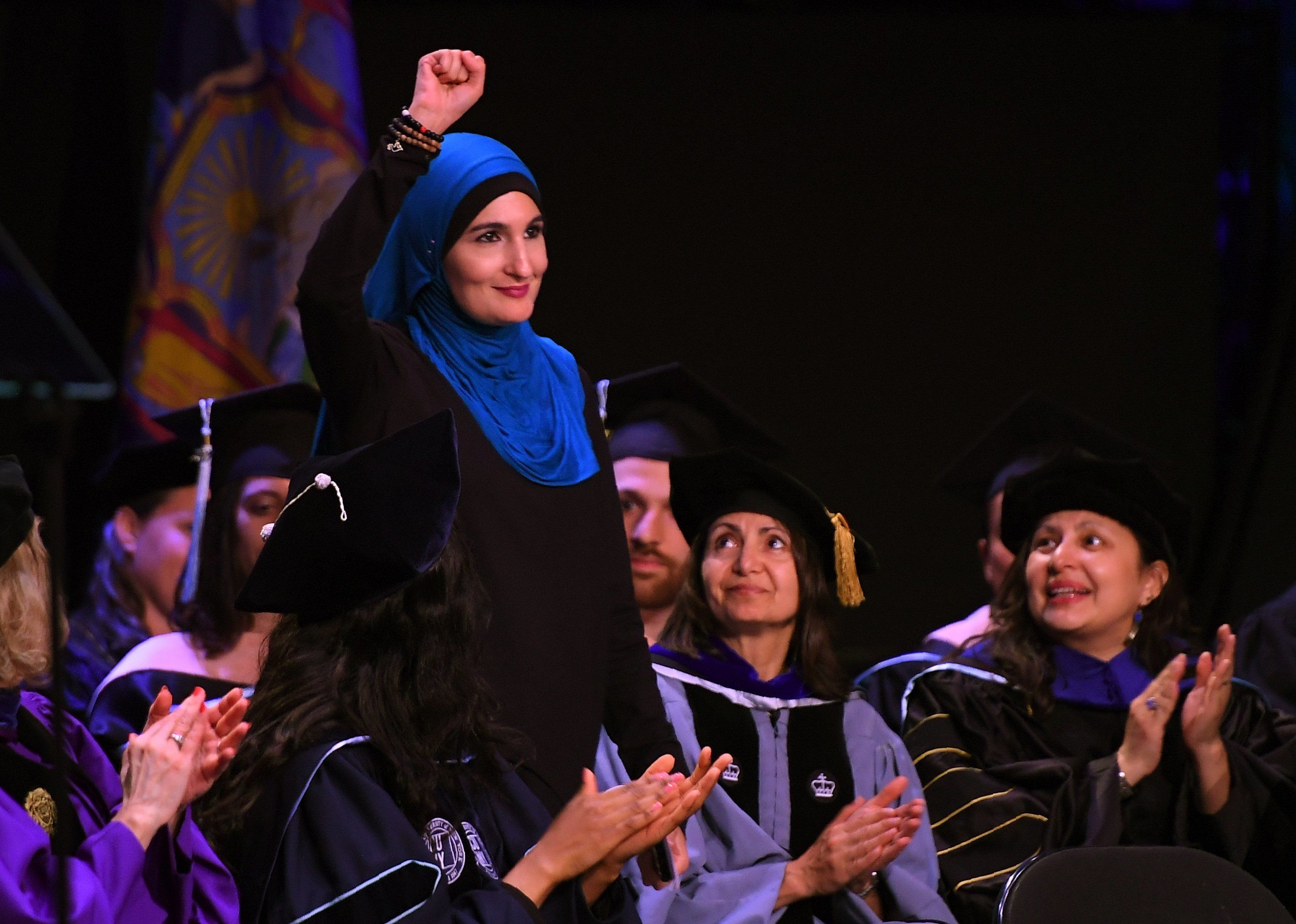 Linda Sarsour raises her fist as she walks to the stage as the keynote speaker at the CUNY Graduate School of Public Healths