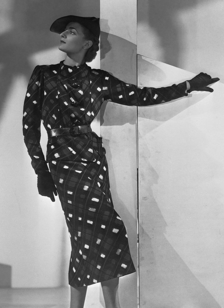 This frock is among the creations (Schiaparelli) chosen by Mrs. Wallis Simpson, to be worn after her 1937marriage to the Duke of Windsor. Mrs. Simpson's flair for sport clothes is demonstrated in the above. It is a crepe marocain, boldly printed in blue, black and white.