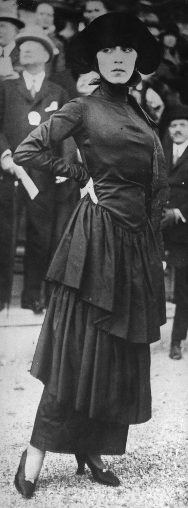 A Poiret model wearing a dress of black marocain with a severe neckline and flounced hobble skirt.