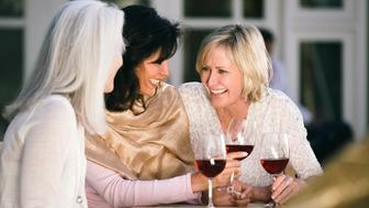 Three beautiful, mature women are sitting at a table in a cafe. Women are drinking red wine. They are having fun, laughing and updating each other on the latest news. Women are between 50 and 65 years old. Cheers!