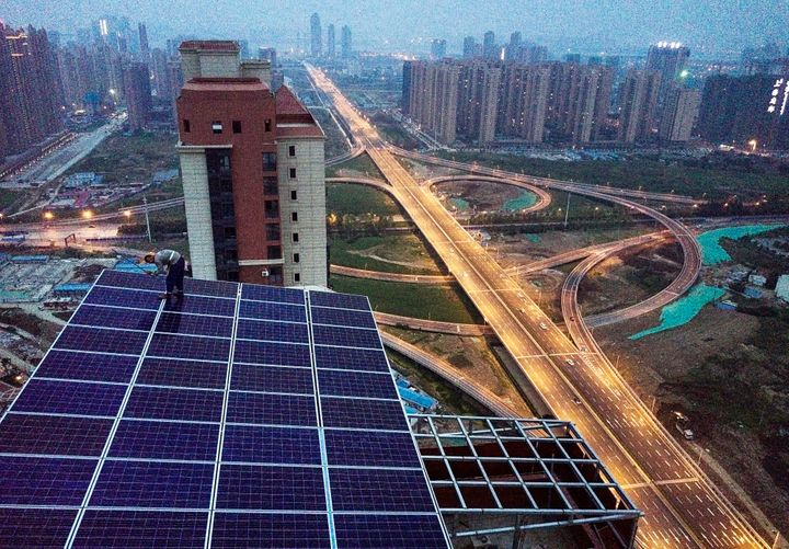 A Chinese worker from Wuhan Guangsheng Photovoltaic Company works on a solar panel project on the roof of a 47 story building