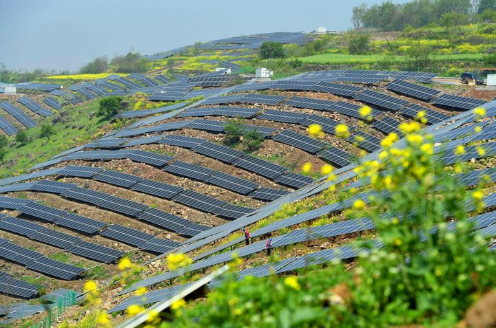Chinese workers check solar photovoltaic modules on a hillside in a village in Chuzhou, which is in eastern China's Anhui pro