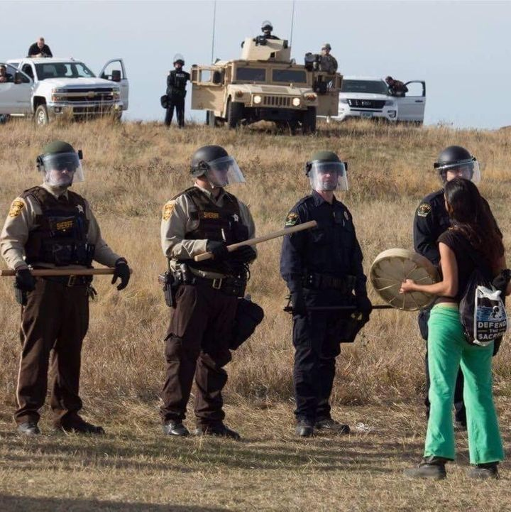 Lolly Beestands near a group of officers in riot gear near the Dakota Access Pipeline construction site in North Dakota
