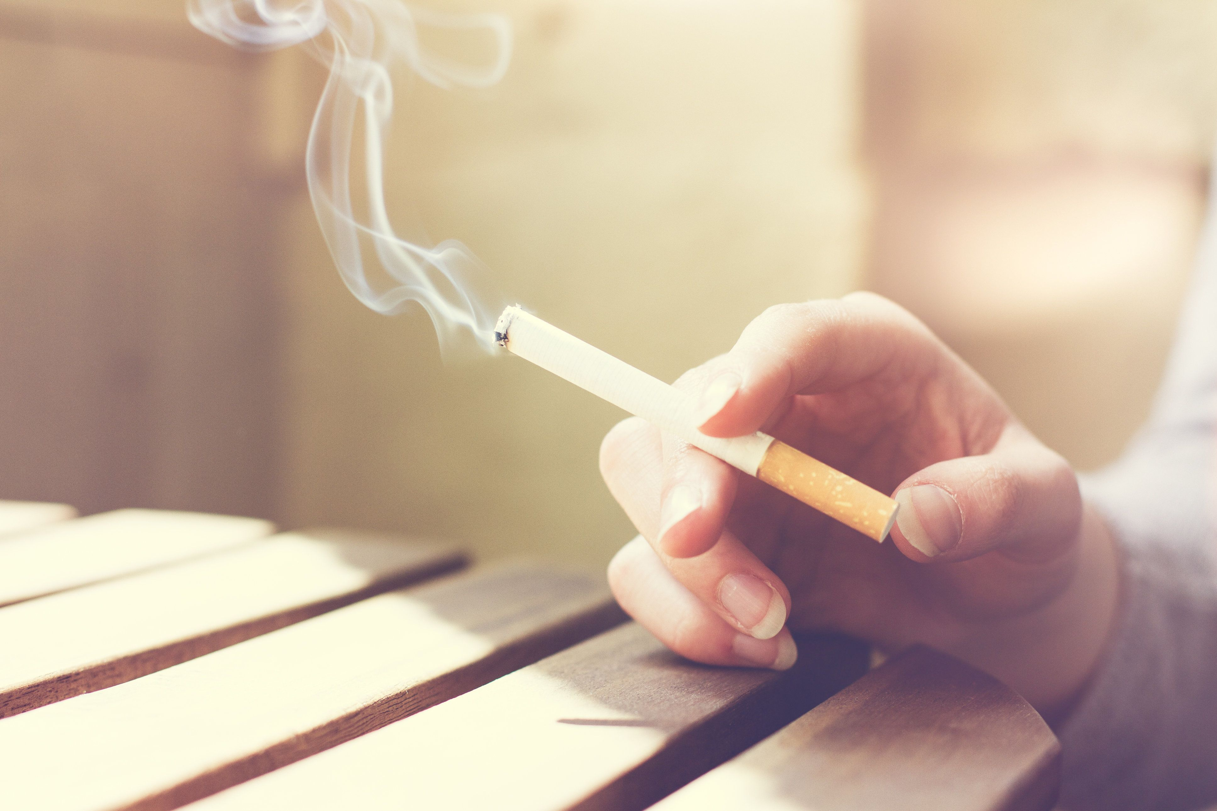 Woman smoker smoking a filter tip cigarette with her hand resting on a slatted wooden table with copy space, close up view