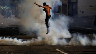 A demonstrator jumps amid tear gas smoke during clashes with riot security forces at a protest against Venezuelan President Nicolas Maduro's government in Caracas, Venezuela May 24, 2017. REUTERS/Marco Bello