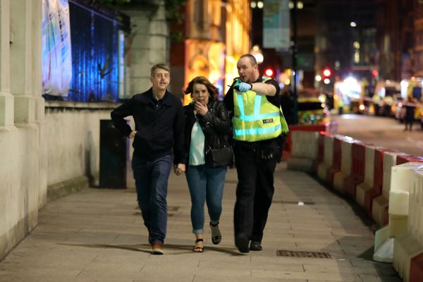 A police officer escorts members of the public to safety at London Bridge