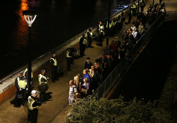 Police officers stand with people evacuated from the area near London Bridge