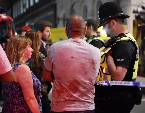 People speak with police officers after an incident near London Bridge.