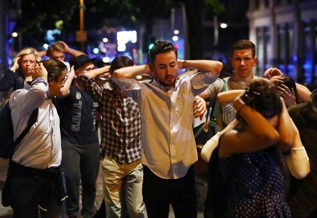 People leave the area with their hands up after an incident near London Bridge in