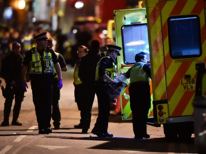 Police officers speak with ambulance personnel after Saturday night's terror incident near London Bridge.