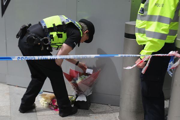 A police officer looks at a floral tribute left by a man near the scene of the terror attacks.