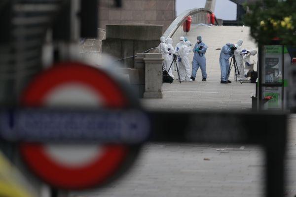 Police forensic officers work on London Bridge.