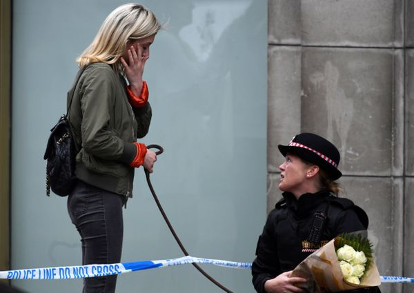 A woman walking her dog reacts near London Bridge while talking to a police officer.