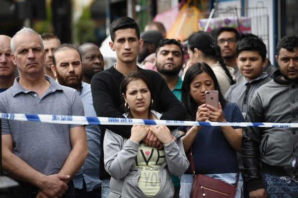 Members of the public view the scene after police officers raided a property in East Ham in London, England.