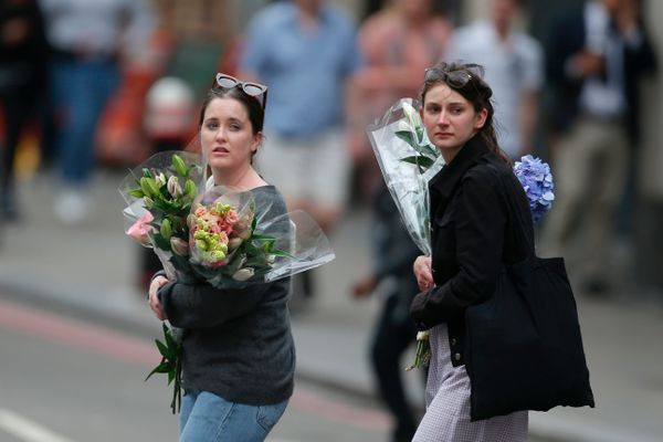 Women arrive at the north end of London Bridge with flowers.