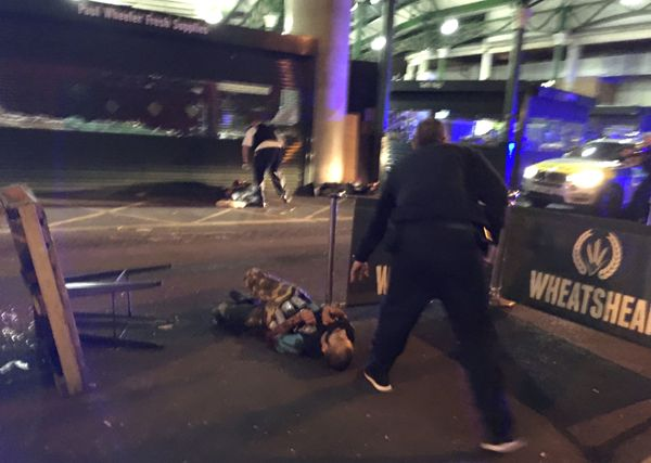 Armed police stand over what is believed to be a suspect shot outside Borough Market