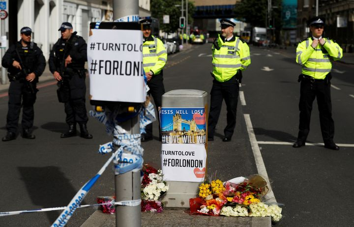 Flowers and messages lie behind police cordon tape near Borough Market after an attack left seven people dead and dozens inju