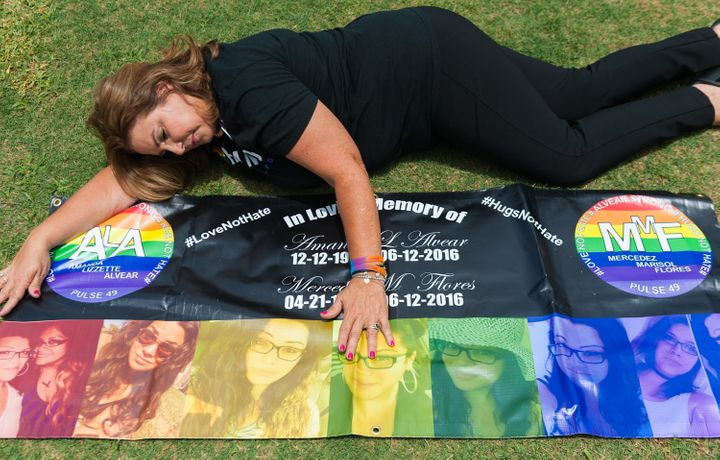 Mayra Alvear poses with a banner she made for her daughter Amanda Alvear and Mercedez Flores both killed in the Pulse nightclub shootings last year.