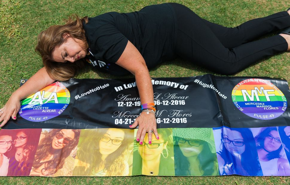 Mayra Alvear poses with a banner she made for her daughter Amanda Alvear and Mercedez Flores both killed in the Pulse nightcl
