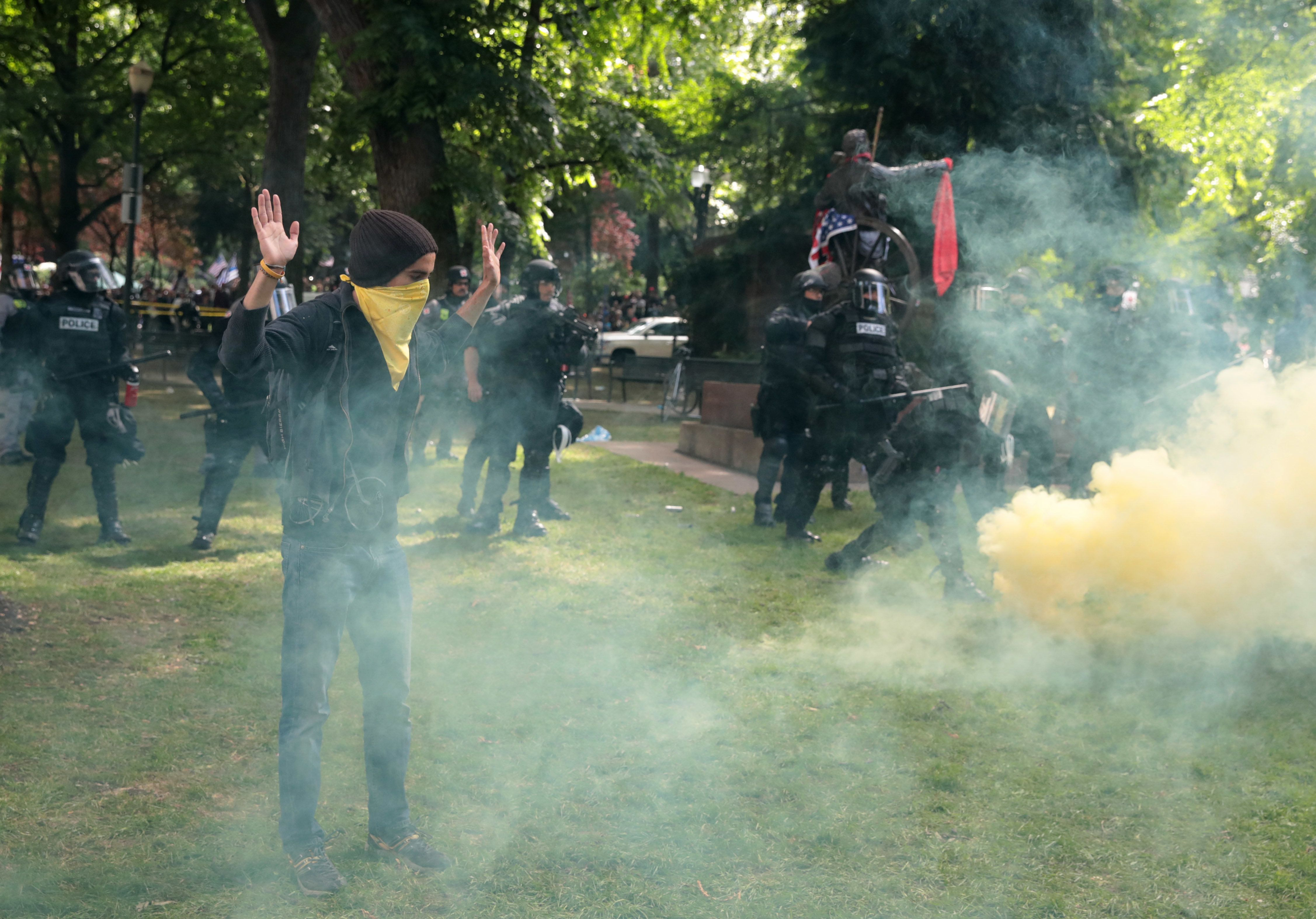 PORTLAND, OR - JUNE 04:  A man raises his hands as police clash with demonstrators as they try to clear 'Antifa' members and anti-Trump protesters from the area during a protest on June 4, 2017 in Portland, Oregon. Police used tear gas, flash bangs, and rubber bullets to clear the crowd. A protest dubbed 'Trump Free Speech' by organizers was met by a large contingent of counter-demonstrators who viewed the protest as a promotion of racism. The demonstrations come in the wake of the recent violent attack on the city's MAX train line when Ricky Best, 53, and Taliesin Namkai-Meche, 23, were stabbed to death and Micah Fletcher,21, was severely injured after they tried to protect two teenage girls, one of whom was wearing a hijab, from being harassed with racial taunts by suspect Jeremy Christian.  (Photo by Scott Olson/Getty Images)
