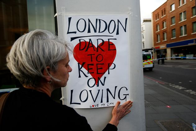 A woman attaches a sign near London