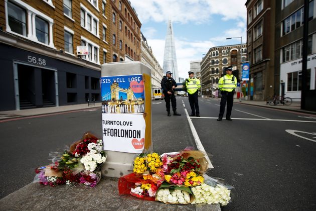 Flowers and messages lie behind police cordon tape near Borough