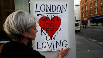 A woman attaches a sign near London Bridge, after attackers rammed a hired van into pedestrians on London Bridge and stabbed others nearby killing and injuring people, in London, Britain June 4, 2017. REUTERS/Peter Nicholls