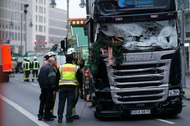 Firefighters stand beside the truck which plowed into a crowded Christmas market in Berlin last December.