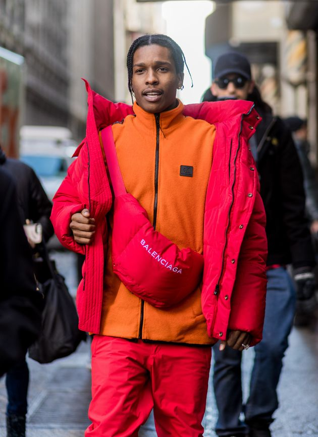 A$AP Rocky wearing a red down feather jacket, Balenciaga bag, orange zip jacket outside Calvin Klein...