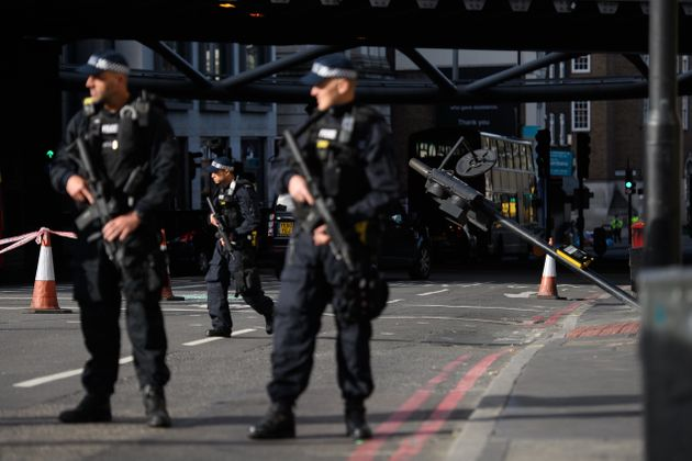Armed police guard the location on London Bridge where terrorists crashed their van before stabbing people...