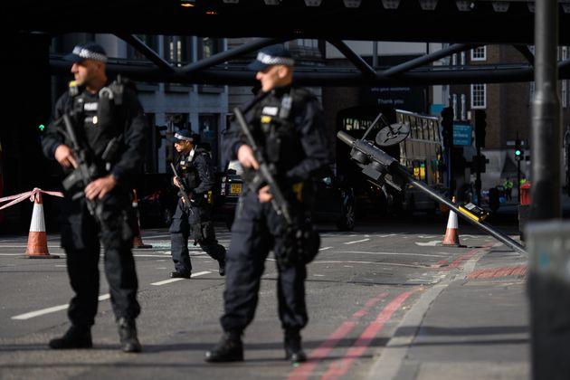 Policiais armados montam guarda no local na London Bridge onde terroristas arremeteram sua van contra pessoas, antes de descerem dela para esfaquear pessoas que curtiam a noite na vizinha Borough Market.