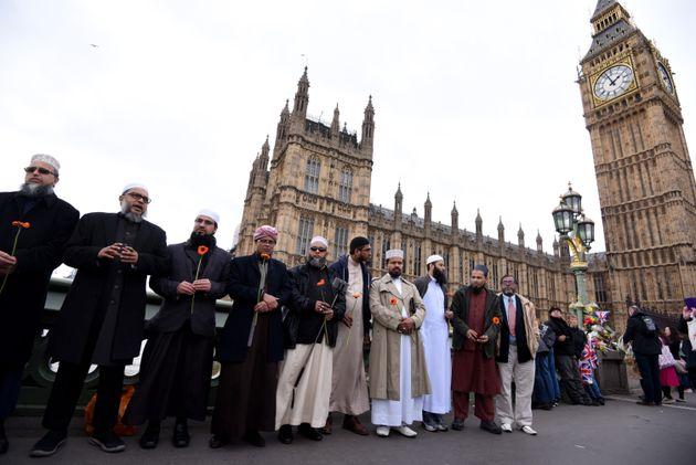 Imãs seguram flores, reunidos na ponte de Westminster antes de uma vigília em memória às vítimas do ataque terrorista da ponte de Westminster.